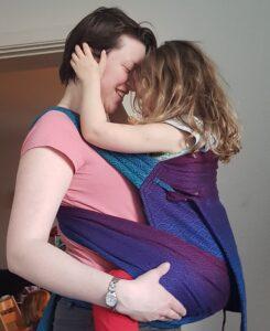 Kærligt øjeblik mellem mor og datter i bæresele på maven.