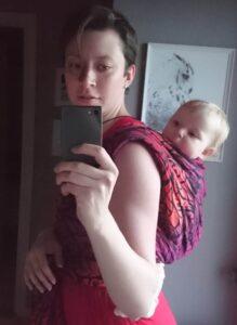Hvid kvinde med barn i vikle på ryggen i Solnce Power. Lige inden julefesten går i gang.