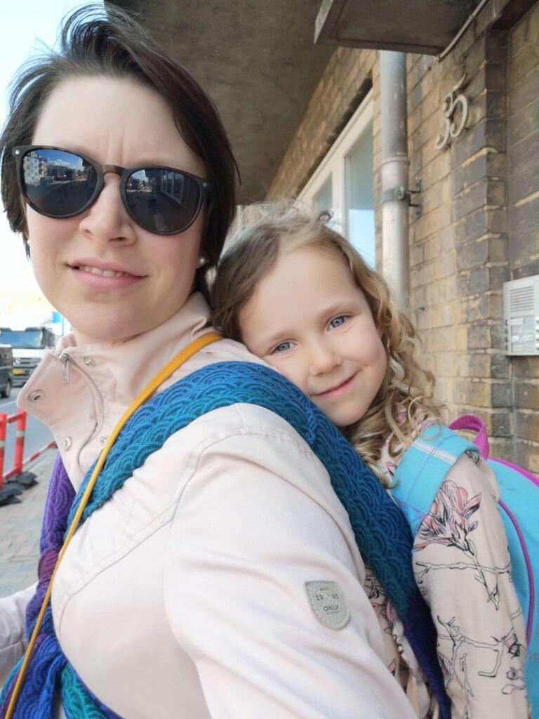 Hvid kvinde med stort barn på ryggen i en Oscha Cairis Carrier bæresele.