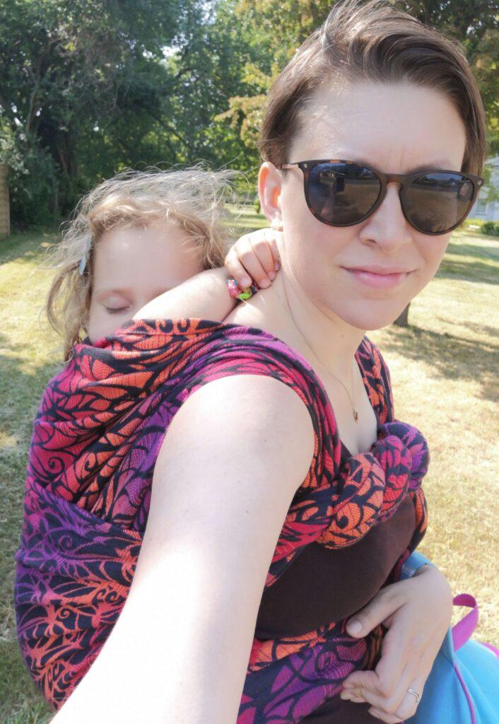 Hvid kvinde med stort barn sovende på ryggen i vikle Solnce Power.