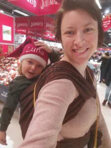 Hvid kvinde med barn i vikle i rygbinding. Barnet har en nissehue på og de er i et supermarked med juleskilte. Vanamo vikle.