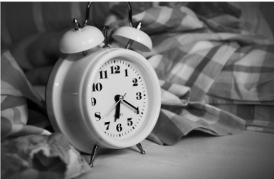 Sort/hvid billede med et alarmur på. God søvn er godt for vores fysiske velvære og god selvomsorg.