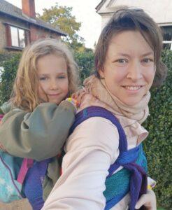 Hvid kvinde der bærer 5 årig hvid pige på ryggen i bæresele